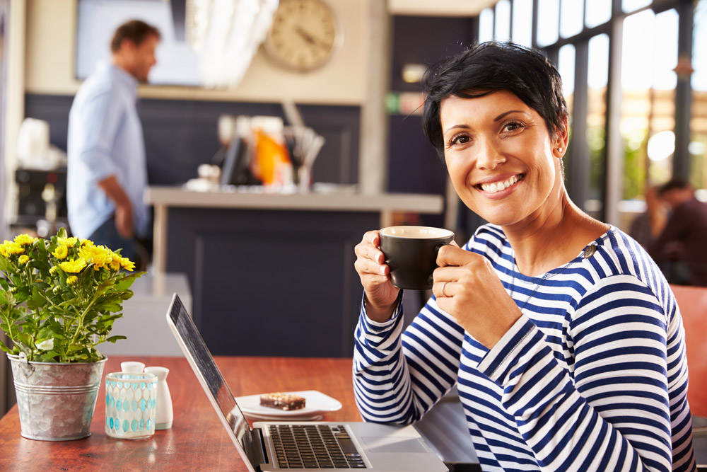 Woman smiling, sitting in coffee shop holding a cup of coffee.