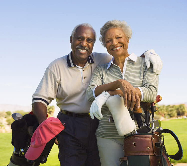 Smiling older couple on golf course. Man has his arm around the woman