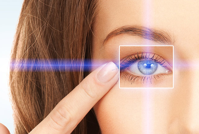 Woman pointing at left eye. Eye has a laser going toward it.