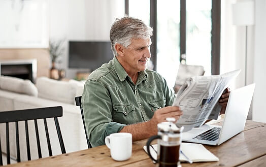 Older man at table reading newspaper