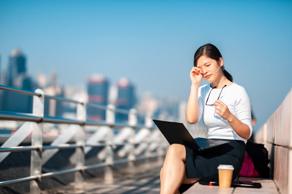 Young woman with dry eyes sitting outside with laptop