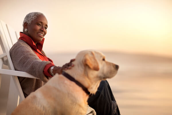 Senior woman at sunset in chair with dog.