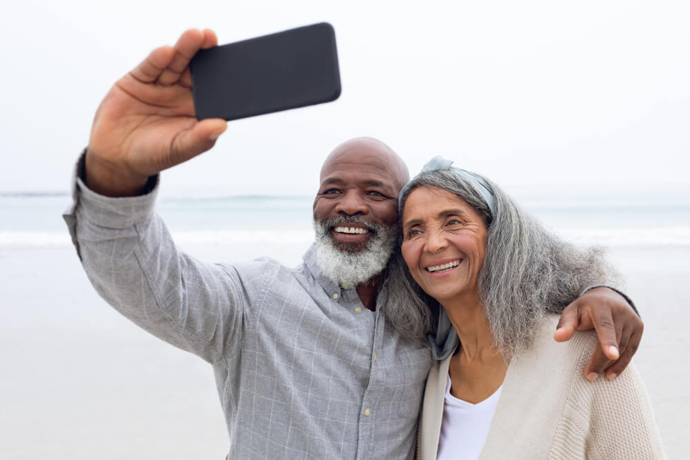 Happy senior couple taking selfie at the beach
