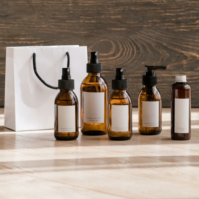 Beauty products and gift bag in front of wood wall