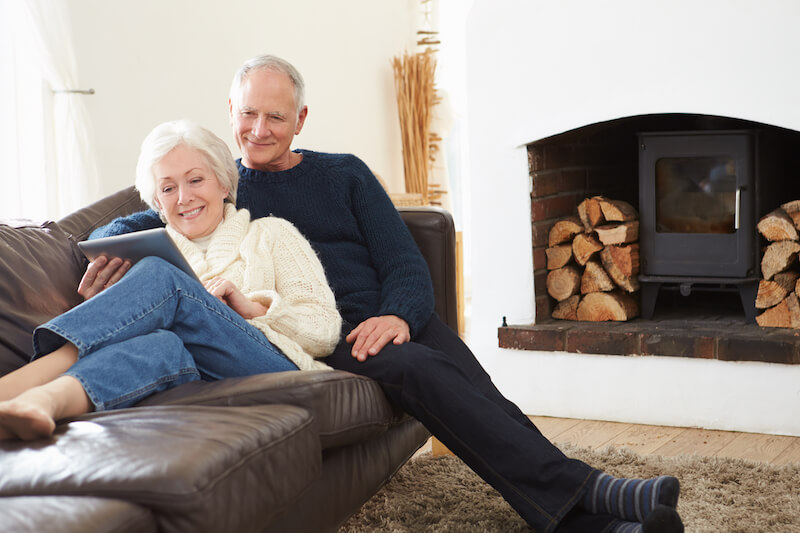 Senior couple on the couch looking at tablet