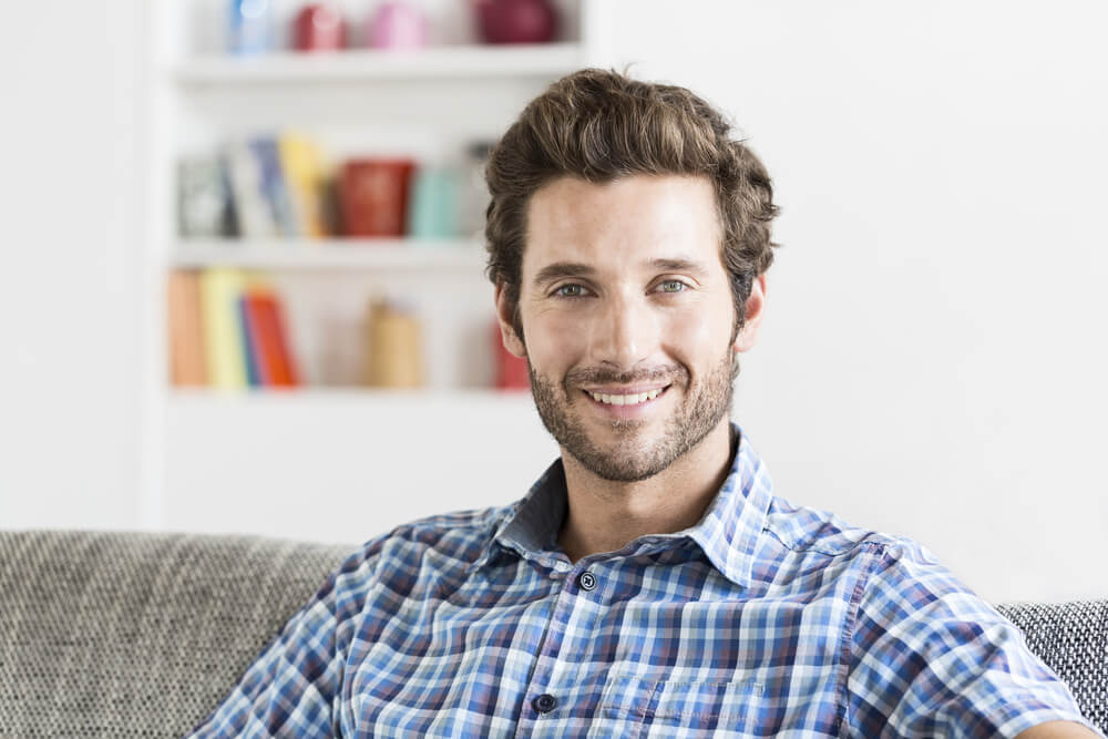Man in his 30s sitting in modern living room