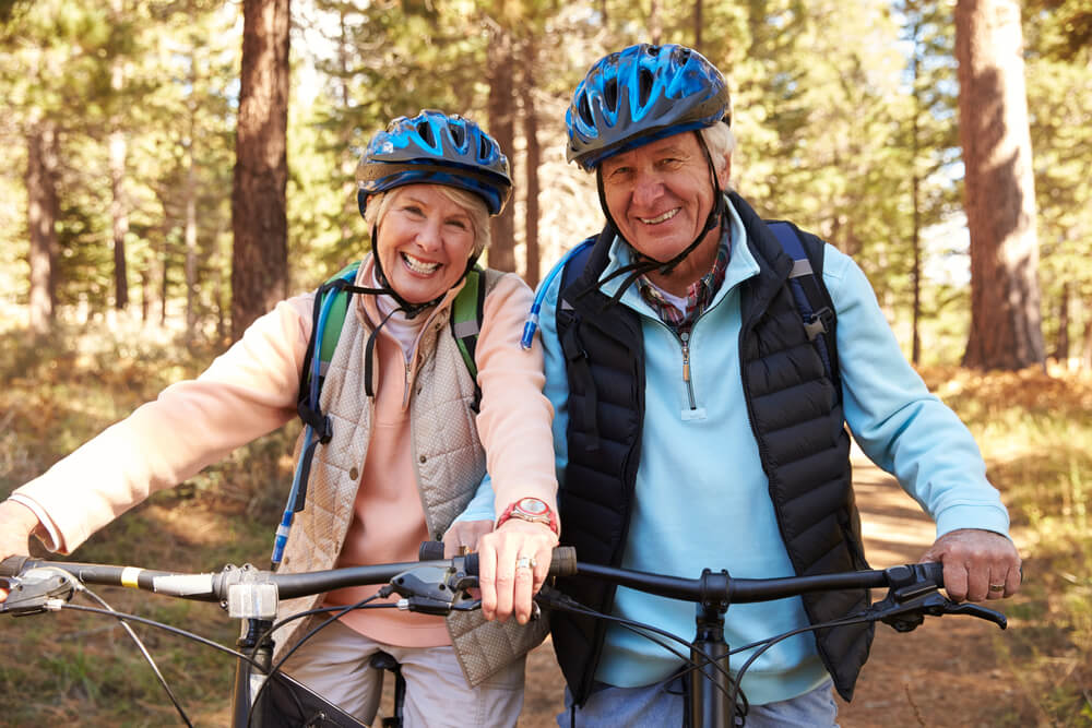 Senior couple on bikes in the woods wearing helmets
