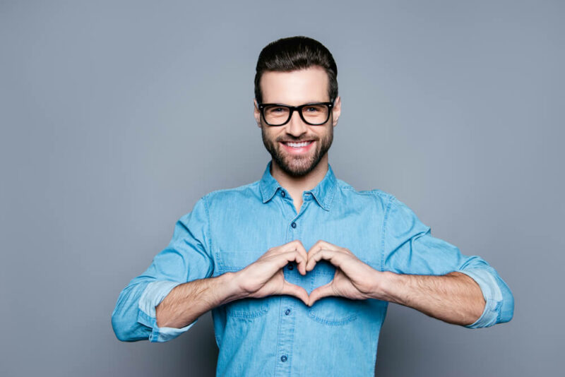 hipster in glasses making a heart with his hands