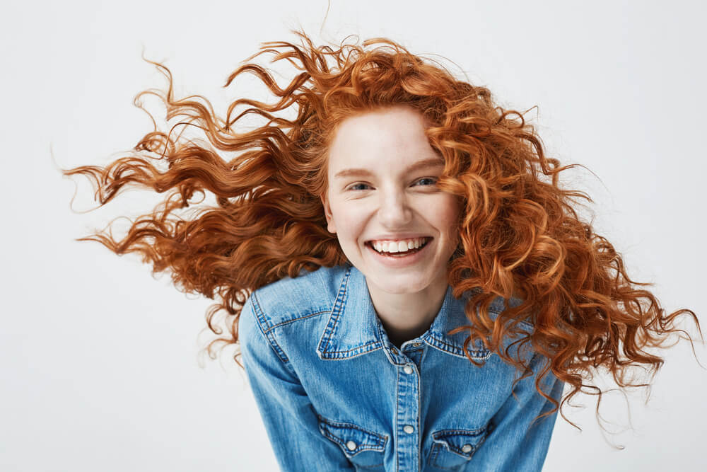 Smiling young girl with bright red hair