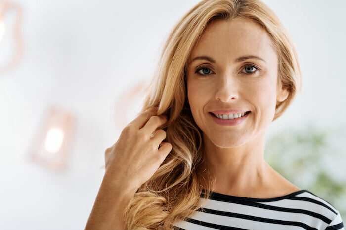 attractive middle-aged blond woman holding hair
