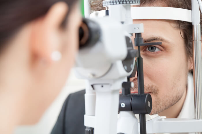 Female eye doctor looking at male patient's eyes